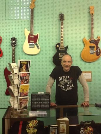Mike Feudale behind the counter – and in front of some must-have-give-me-right-now guitars – at Mike's Monster Guitar.